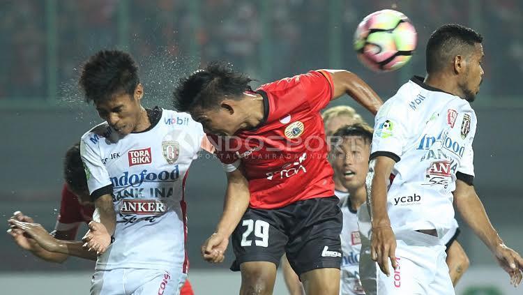 Duel udara antara pemain Persija, Sandi (tengah) dengan Fadil Sausu. Copyright: Herry Ibrahim/Indosport