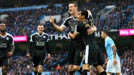 Robert Huth dan Shinji Okazaki berpelukan merayakan gol untuk Leicester City. - INDOSPORT