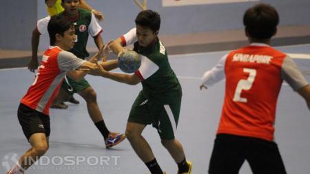 Pemain Indonesia (tengah) mendapat penjagaan ketat dari pemain Singapura. - INDOSPORT