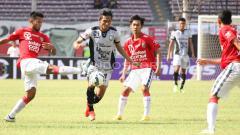 Indosport - Aksi pemain Sriwijaya dan Bali United berebut bola.