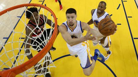 Klay Thompson Golden State Warriors (putih) coba diadang Ed Davis dari Portland Trail Blazers. - INDOSPORT