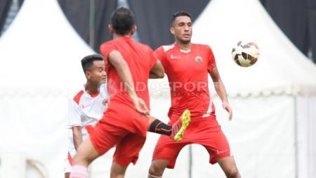 Pemain belakang Persija Jakarta, William Pacheco (kanan) berebut bola dengan salah satu official team. - INDOSPORT