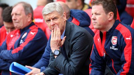 Arsene Wenger sedang duduk di bangku cadangan Arsenal. - INDOSPORT