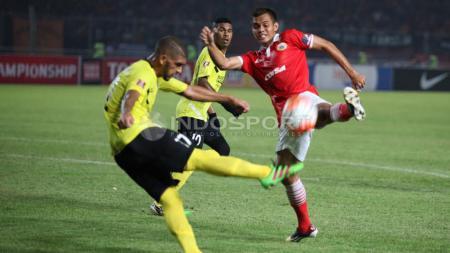 Pemain Persija Jakarta, Rezaldi Hehanusa (kanan) mencoba menghalau tendangan pemain Semen Padang. - INDOSPORT