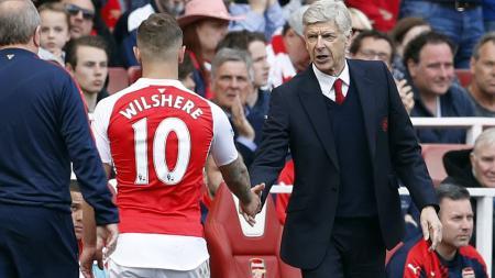 Arsene Wenger berjabat tangan dengan Wilshere. - INDOSPORT