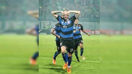 Pemain asing Madura United, Dane Milovanovic melakukan selebrasi wajah 'Batman'. - INDOSPORT
