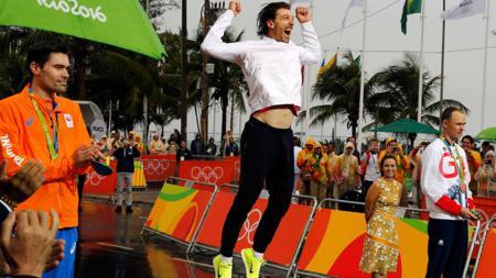 Fabian Cancellara (tengah) melompat girang saat meraih emas Olimpiade 2016. - INDOSPORT