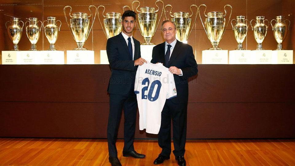 Marco Asensio dan Florentino Perez, dengan background koleksi trofi Liga Champions. Copyright: INTERNET