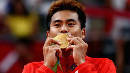 Tontowi Ahmad mencium medali emas. - INDOSPORT