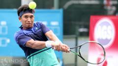 Indosport - Petenis Indonesia, Christopher Rungkat mengembalikan bola ke arah lawannya petenis Jepang, Ken Onoda pada babak kedua turnamen tenis Indonesia AGS-Nassau Men
