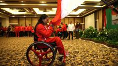 Indosport - Atlet angkat berat, Ni Nengah Widiasih saat mencium bendera Merah Putih di pelepasan kontingen National Paralympic Committee (NPC) Indonesia, di Solo.