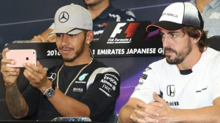 Lewis Hamilton (kiri/Mercedes) lebih memilih bermain Snapchat, sedangkan Fernando Alonso (McLaren-Honda) tetap fokus pada konferensi pers. - INDOSPORT