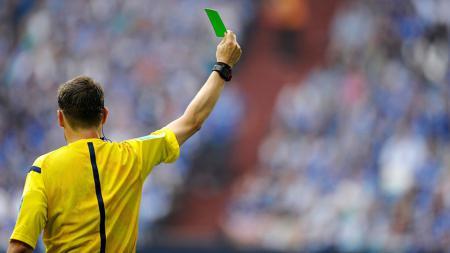 Wasit mengeluarkan kartu hijau dalam sebuah pertandingan sepakbola. - INDOSPORT