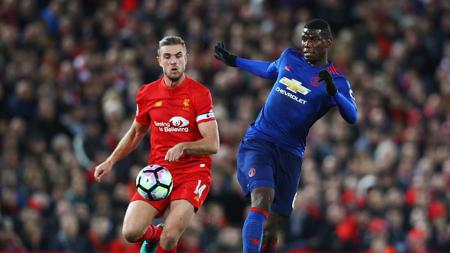 Paul Pogba berduel dengan gelandang Liverpool, Jordan Henderson di Stadion Anfield. - INDOSPORT