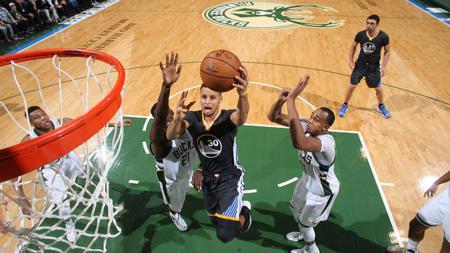 Stephen Curry memasukan bola ke ring basket. - INDOSPORT