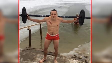 Seorang netizen dari rusia mengangkat besi di tengah-tengah kolam es. - INDOSPORT