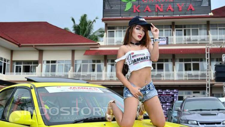 Salah satu wanita sexy pose di atas mobil saat pemotretan event Komunitas Jambore Nasional Lancer Indonesia.