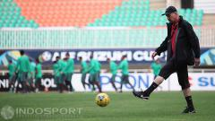 Indosport - Pealtih Timnas Indonesia, Alfred Riedl menendang bola dalam sesi latihan.