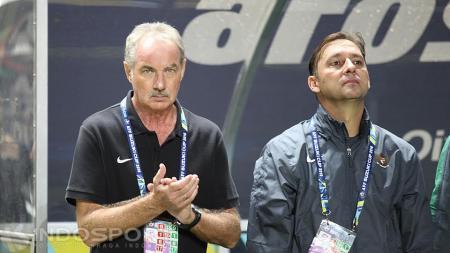 Mantan Pelatih Timnas Indonesia, Alfred Riedl (kiri) dan asisten pelatihnya. - INDOSPORT
