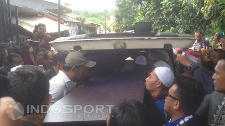 Peti  jenazah Achmad Kurniawan dikeluarkan dari mobil ambulans. - INDOSPORT