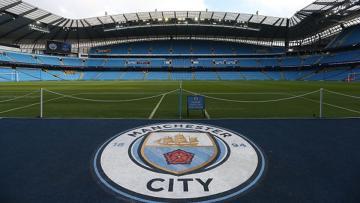 Logo Manchester City terbentang di Etidah Stadium.