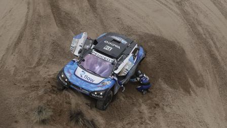Romain Dumas beserta Alain Guehennec berusaha mengeluarkan mobil yang terjebak di pasir.