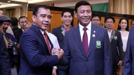 Ketua KONI Tono Suratman (kiri) berjabat tangan dengan pengurus baru PBSI Wiranto. - INDOSPORT