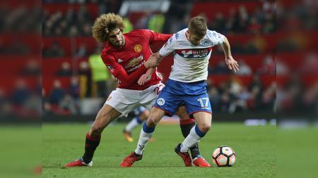 Marouane Fellaini berusaha menjaga pemain Wigan Athletic saat pertandingan babak keempat Piala FA. - INDOSPORT