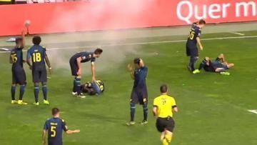 Dua pemain Moreirense terjatuh setelah terkena petasan.