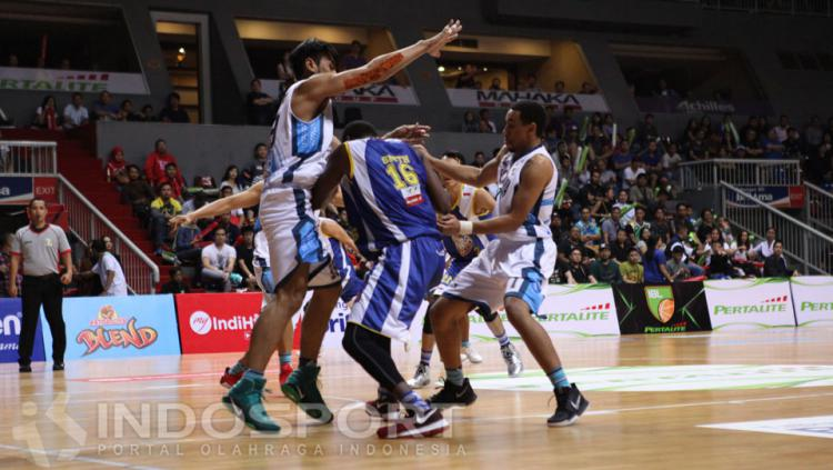 Pemain Satria Muda, Smith Carlos berusaha melewati penjagaan ketat pemain Pelita Jaya.