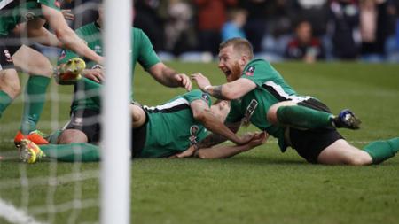 Selebrasi para pemain Lincoln City usai mencetak sejarah di Piala FA. - INDOSPORT