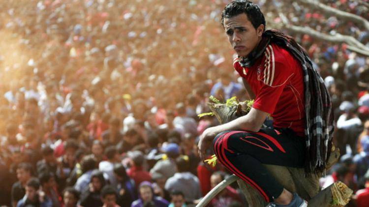 Salah satu pendukung (Ultras) duduk di atas tunggul pohon. Copyright: MAHMUD KHALED/AFP/Getty Images