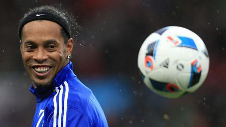 Ronaldinho tengah tersenyum melihat bola. - INDOSPORT