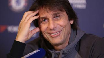 Antonio Conte tersenyum saat konferensi pers.