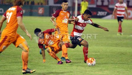 Seorang pemain Madura United dihalangi pergerakannya oleh tiga pemain PBFC.