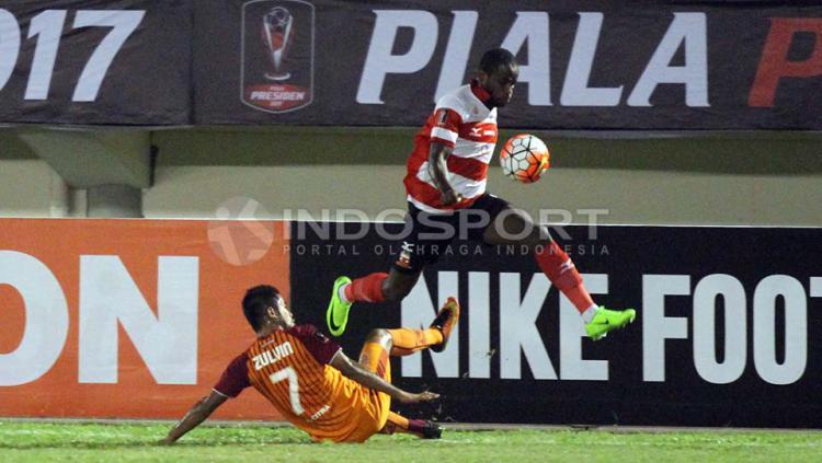 Zulvin Zamrun melakukan tackle ke arah seorang pemain Madura United