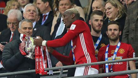 Paul Pogba memberikan trofi Piala Liga Inggris kepada pelatihnya Jose Mourinho.