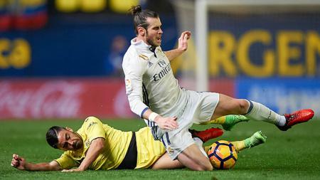 Jaume Costa (kiri) berusaha merebut bola dari Gareth Bale sehingga mengakibatkan jatuh. - INDOSPORT
