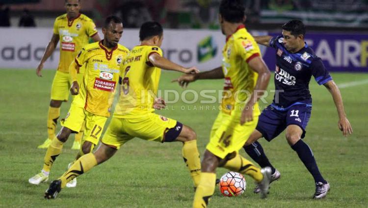 Esteban Gabriel Vizcarra (Arema FC) berusaha melewatkan beberpapa pemain Sriwijaya FC yang menghalaunya.