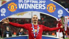 Indosport - Zlatan Ibrahimovic pose dengan background Man United Juara Piala Liga Inggris.