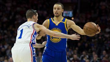 Stephan Curry berusaha melawati pemain Philadelphia 76ers.