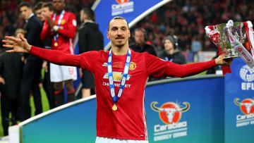 Penyerang andalan Manchester United, Zlatan Ibrahimovic sedang pamer trofi Piala Liga Inggris.