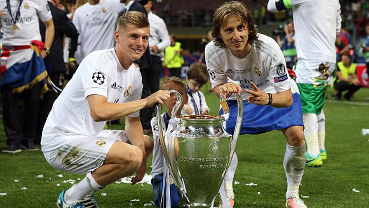 Toni Kroos (kiri) dan Luka Modric pose bersama trofi Liga Champions. Copyright: Chris Brunskill Ltd/Getty Images