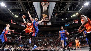 Pemain Detroit Pistons menghalau LeBron James yang akan memasukkan bola ke dalam jaring.