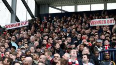Indosport - Fans Arsenal membentangkan poster dengan tulisan, Wenger Out.