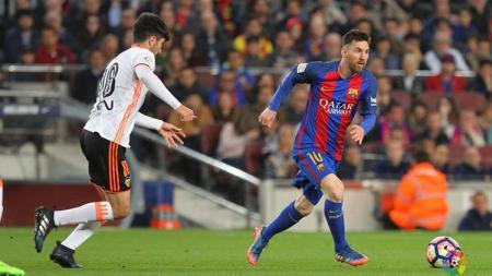 Lionel Messi mencoba melewati hadangan pemain Valencia. - INDOSPORT