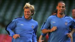 Indosport - David Beckham (kiri) bersama dengan Rio Ferdinand kala masih membela Timnas Inggris.