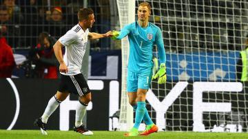 Lukas Podolski (kiri) dan Joe Hart di laga persahabatan Jerman vs Inggris.