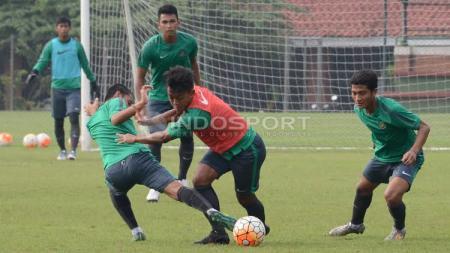 Febri Hariyadi (tengah) berhasil melewati hadangan Evan Dimas. - INDOSPORT