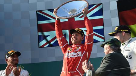 Pembalap Ferrari, Sebastian Vettel mengangkat trofi setelah menangi balapan GP Australia. - INDOSPORT